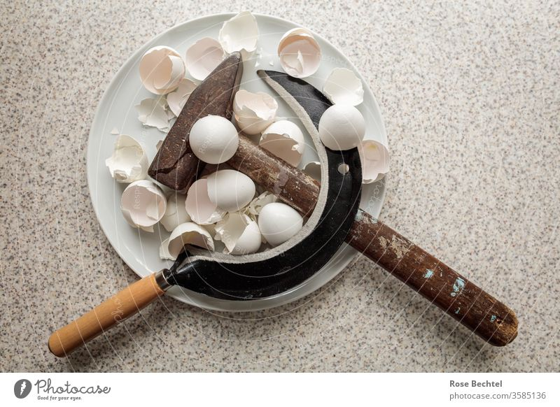 Hammer and sickle on a plate with egg shells Metal Brown Colour photo Shatter Tool Symbols and metaphors hammer and sickle object of desire Plate Eggshell