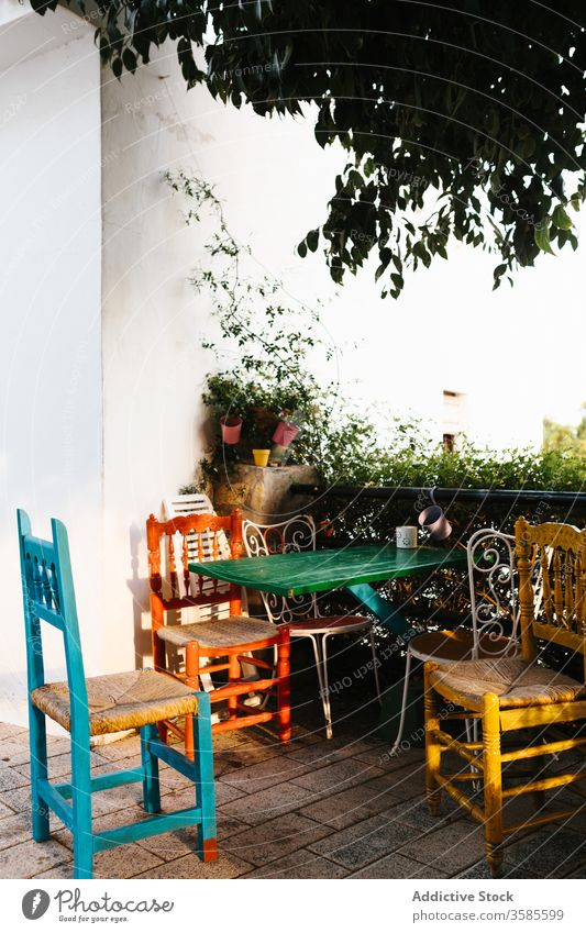 Picturesque table with chairs on terrace with green plants countryside house veranda colorful metal fence ivy home cottage building exterior picturesque set