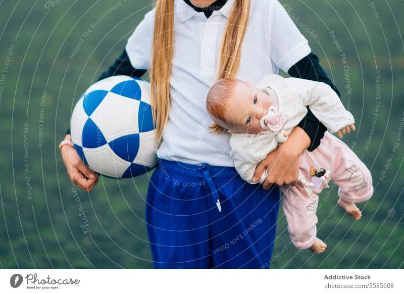 Crop determined girl with soccer ball and doll on field choice football kid stereotype sport child concept uniform game toy training equipment jersey player