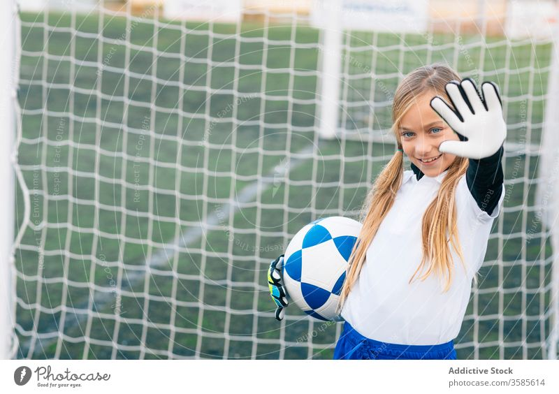 Happy young female player with ball in football arena at sports stadium girl soccer field uniform happy child kid club childhood athlete equipment smile preteen
