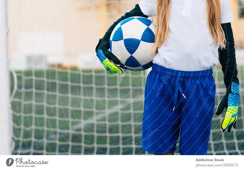 Crop young female player with ball in football arena at sports stadium girl soccer field uniform child kid club childhood athlete equipment preteen schoolgirl