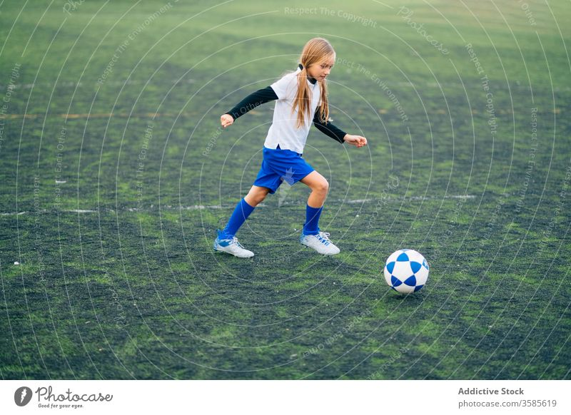Focused young female player playing football at sports stadium girl soccer field kid run uniform club training child game activity athlete equipment kick