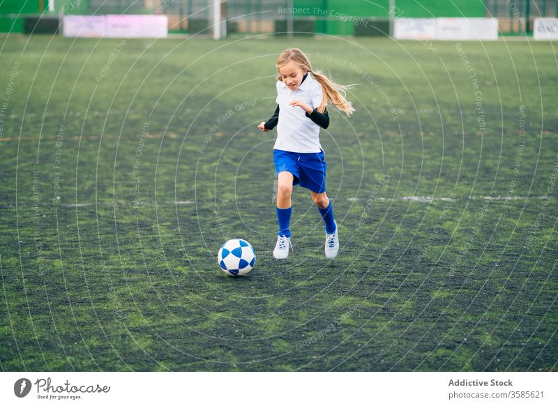 young female player playing football at sports stadium girl soccer field kid run uniform club training child game activity athlete equipment kick focus