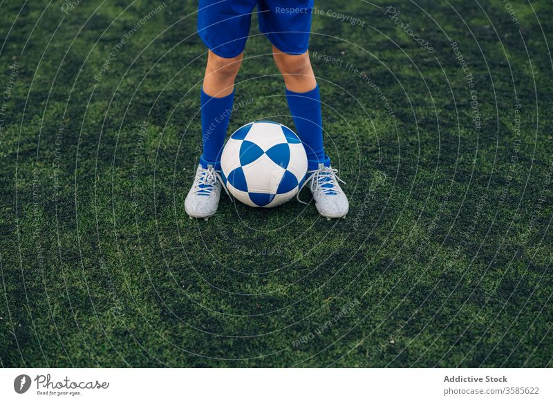 Crop kid in blue uniform with soccer ball on green field in contemporary sports club child football player leg cleats court stadium training athlete jersey game