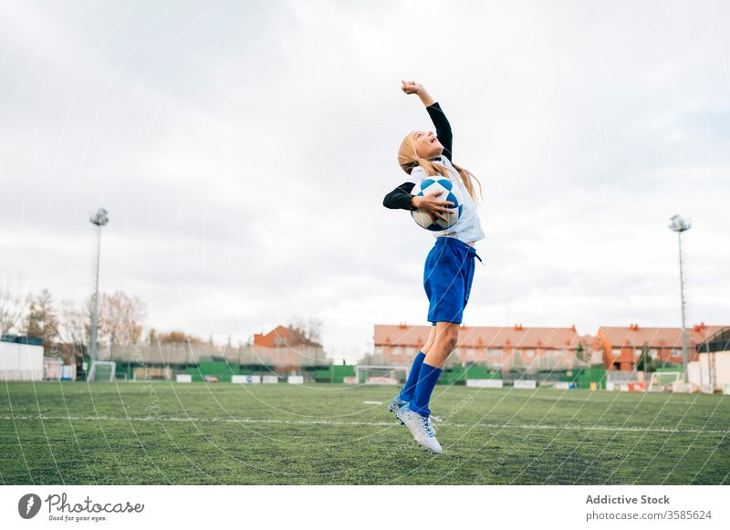 Happy young female player rejoicing in success while playing football at sports stadium girl soccer win kid celebrate goal victory happy field triumph rejoice