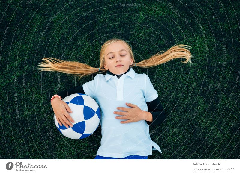Cheerful girl player with soccer ball relaxing on lawn laugh field football ponytail stadium child kid preteen happy playful optimist uniform equipment sporty