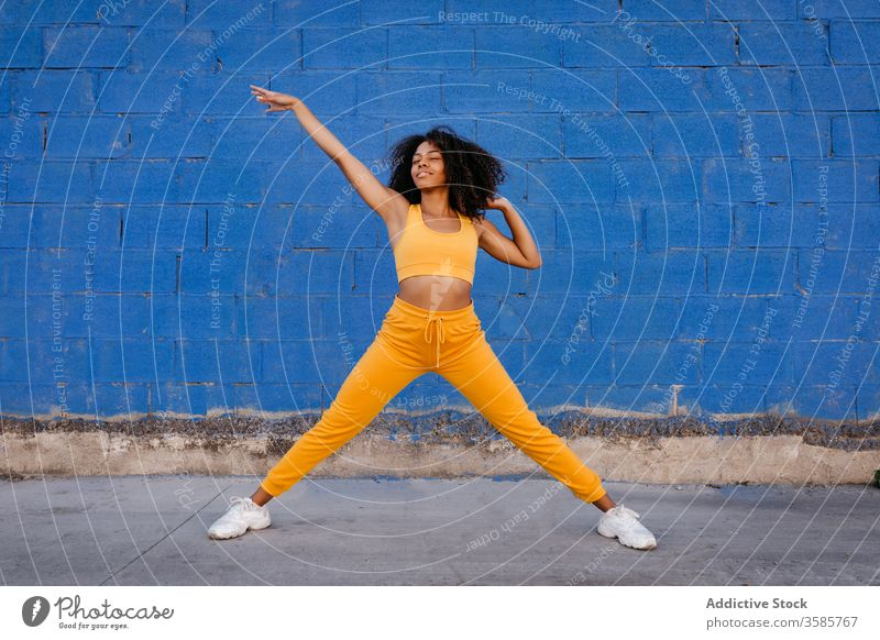 Cheerful African American woman with afro hairstyle in dancing pose dance move vivid vibrant cheerful smile motion color female black ethnic african american