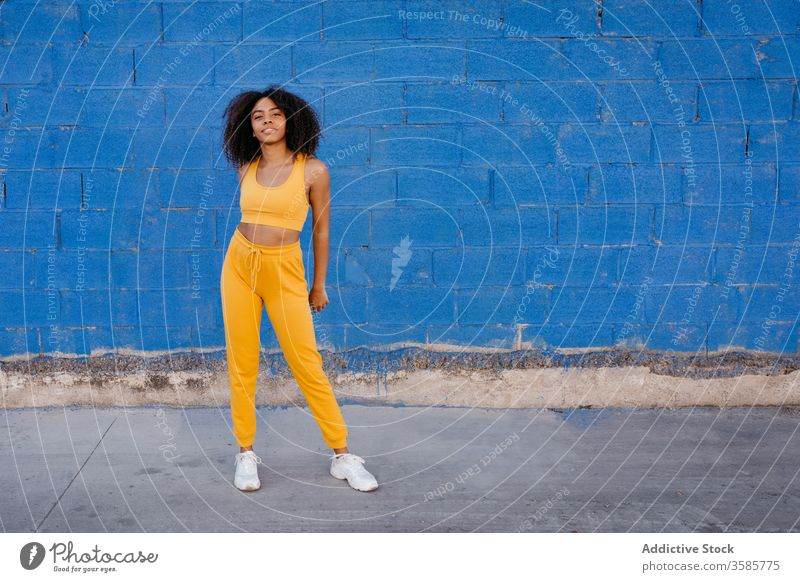 Cheerful African American woman with afro hairstyle in a carefree pose move vivid vibrant cheerful smile motion color female black ethnic african american