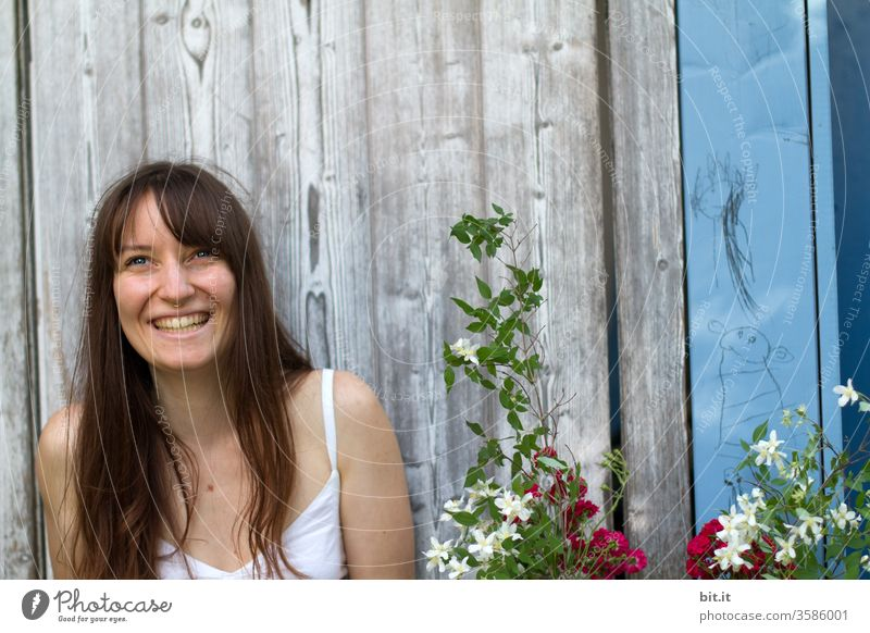 Laughing, long-haired young woman sits in front of an old wooden wall outside in the garden and is happy about a flower gift from a party guest. Happy, natural, brunette young adult with a beaming face at garden party Party Party in party mood laughs joyfully.