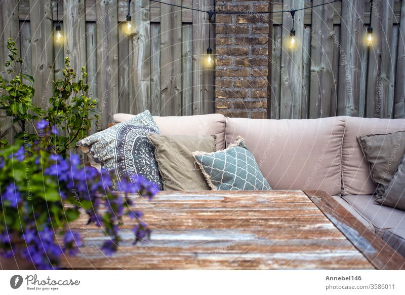 Stylish outdoor garden furniture, sofa with cushions and lamps, light bulbs hanging, cozy modern corner on terrace flower background family spa design tree