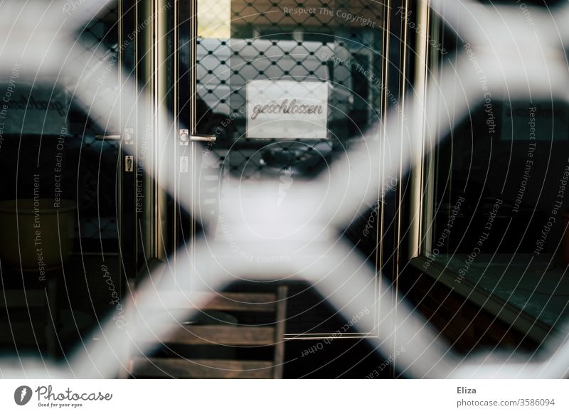 The barred door of a shop with a closed sign hanging from it Closed business Retail sector latticed Economy Load Crisis bankrupt Insolvency