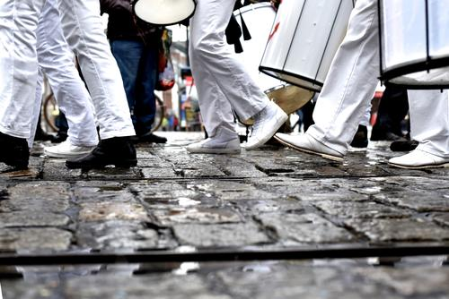 people dressed in black and white walk over cobblestones - it has rained but the train continues Legs Black White garments Going March Drum marching formation