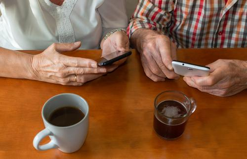 Top view of old people using smartphones at home while enjoying cups of hot drinks. Concept of elderly people and technology. senior mobile use happy person