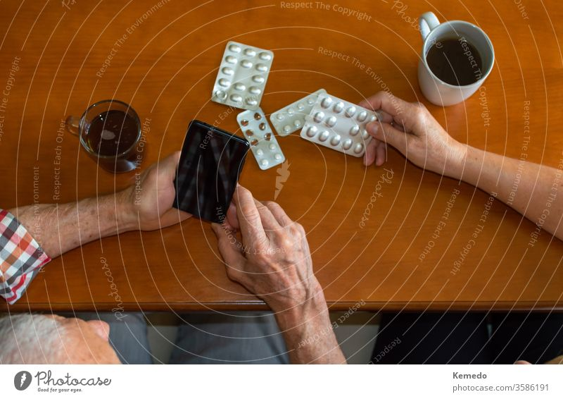 Top views of elderly people using mobile phones to answer medical questions at home while enjoying hot drinks. Old people and use of technology for medical reasons.