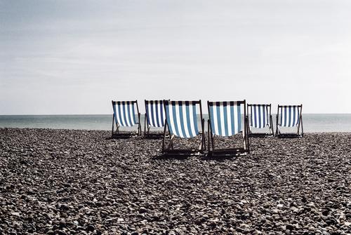 Blue striped deck chairs on a British pebble beach brighton great britain no one empty nobody rental united-kingdom coastal water peaceful seasonal blue stripes