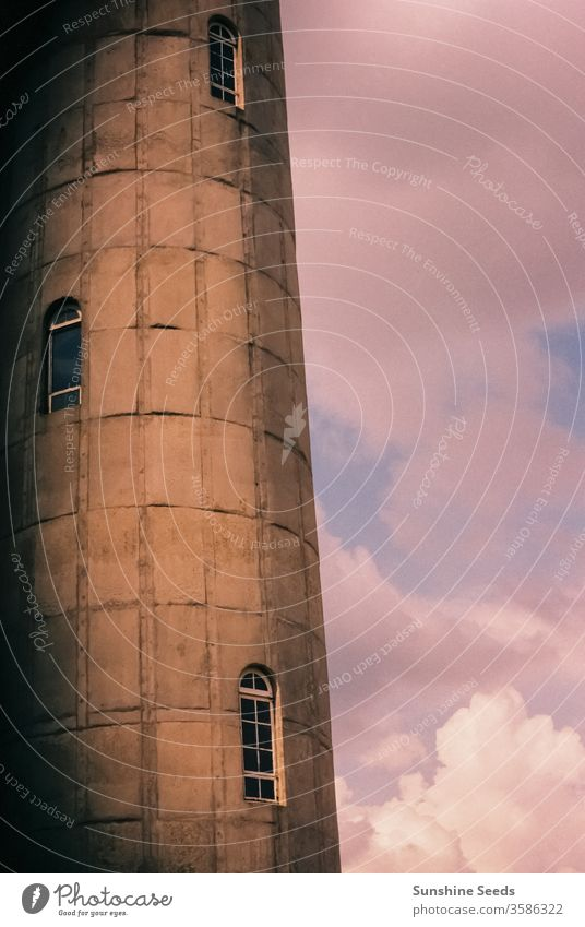 Partial view of an old water tower made from bricks town city vintage art deco retro windows architecture building blocks pink purple reserve grunge tank sky