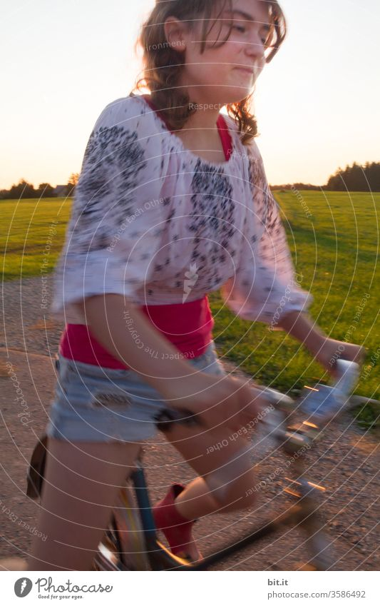 Smiling, the brunette teenager, in a fashionable blouse and shorts, pedals on the pedals, grinning cheekily. Summery, fast, dynamic bike ride on the road, past green grass of a meadow and trees, with blurred by the movement.