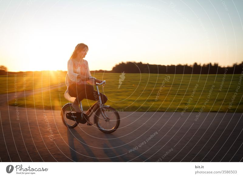 Long-haired, brunette teenagers, riding a small bicycle on the street in the evening light. Cycling in the twilight, passing green meadows and woods, the teenager, like a funny giant on the oversized, tiny dwarf bike.