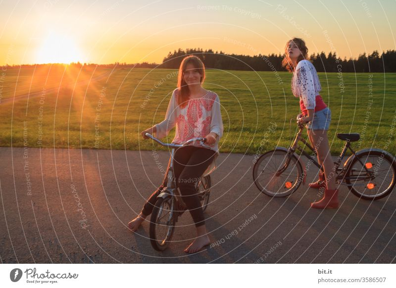 Two long-haired, brunette teenagers, with fashionable, pretty blouses in hippie style, sit and stand on the street with old, nostalgic bicycles. 2 sisters pose in the evening sun with their bikes, in front of green meadows, in nature, on the street.