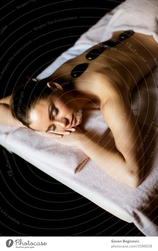 Young woman having a hot stone massage therapy alternative back beautiful beauty black body calm care caucasian clean clinic close concept dayspa enjoying