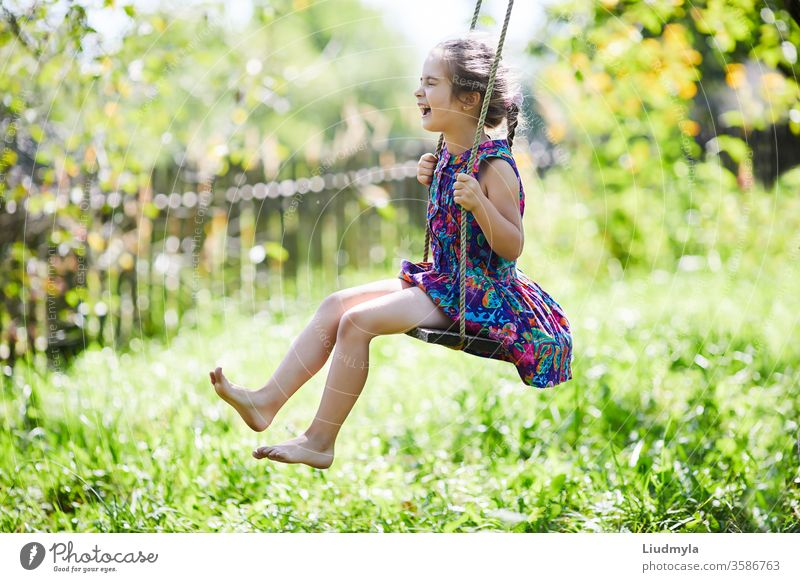 Happy little girl is smiling and  swinging  in the garden in a sunny summer day. laugh funny outdoor smile summertime lifestyle emotions sit tree exercise