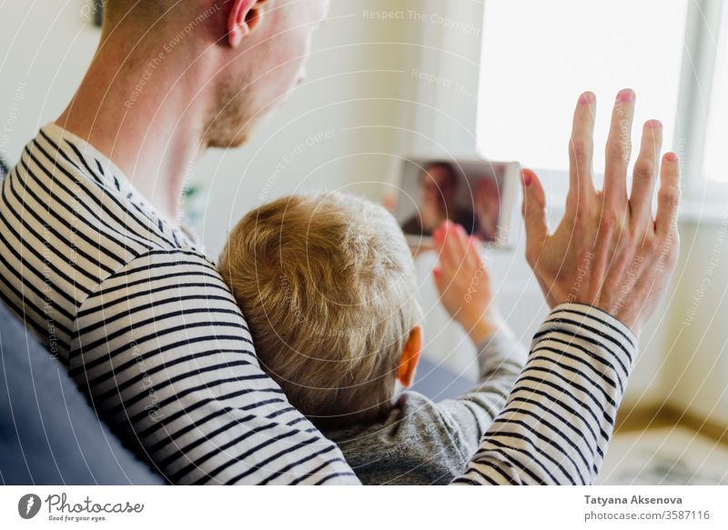 Father and son having video call to mother family internet technology modern people home chat computer communication woman young happy online wireless