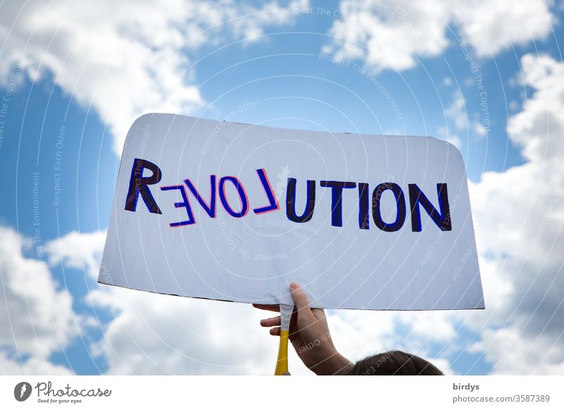 Revolution in the spirit of love. Demonstrator with shield propagates change in the sense of humanity, equality and charity Love Humanity Demonstration