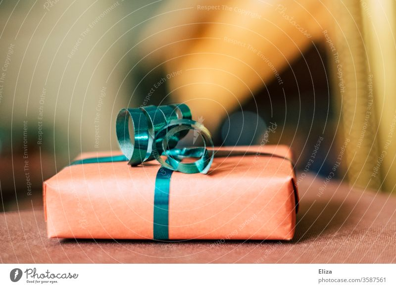A gift with a gift ribbon for Christmas or a birthday in front of a blurred background. Gift Donate Birthday Mother's Day Gift wrapping Packaged