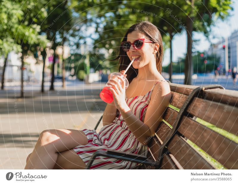 Cute woman in the street. She is drinking a cold tea in the summer. She is wearing sunglasses. outdoor girl people young wellness active blue adult female women