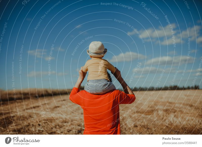 Rearview Mother with Son on shoulders motherhood Baby Shoulder Rear view Red Field fields Walking Caucasian Lifestyle Family & Relations Child Happiness Cute