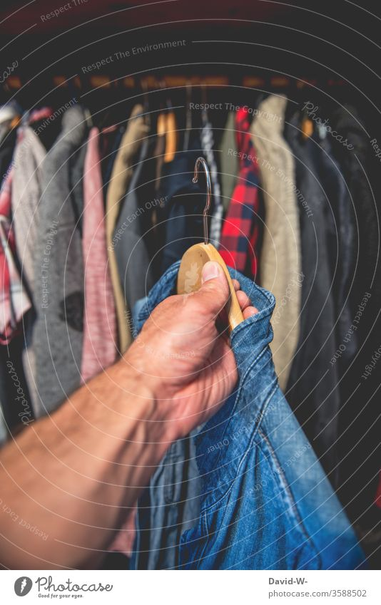 a blue shirt from the wardrobe by hand garments Attract Closet Hallstand Shirt Grasp Decide Clothing Fashion Interior shot Style hang Hanger Colour photo