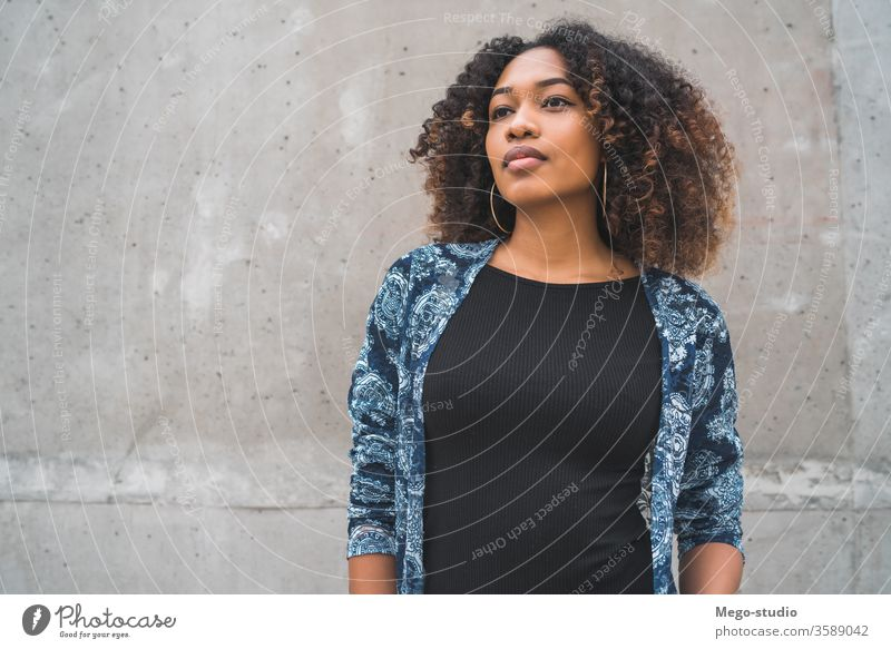 Afro-american woman against grey wall. afro young girl face expression adult looking fashion black standing smiling confident hair brunette model beautiful