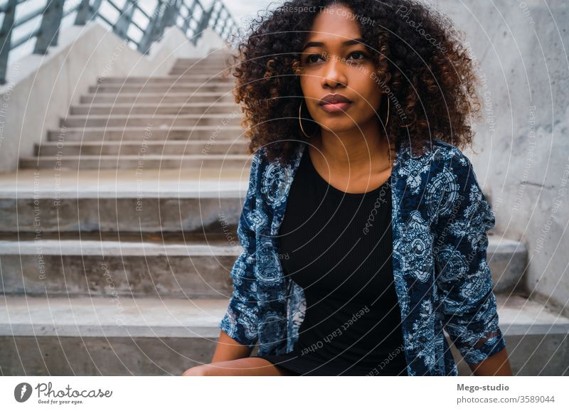 Afro-american woman sitting on steps. afro grey young girl face wall expression adult looking fashion black standing smiling confident hair brunette model