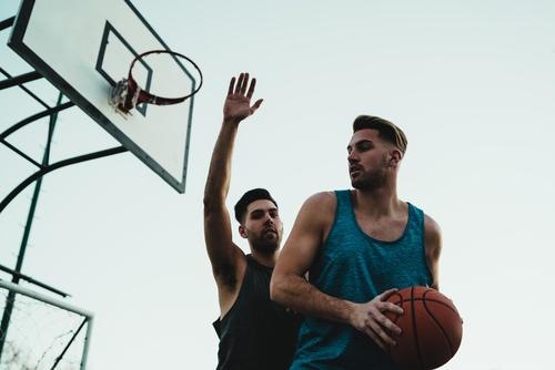 Young basketball players playing one-on-one. game youth sport court male young team together active action playground exercise men friendship jump happy athlete
