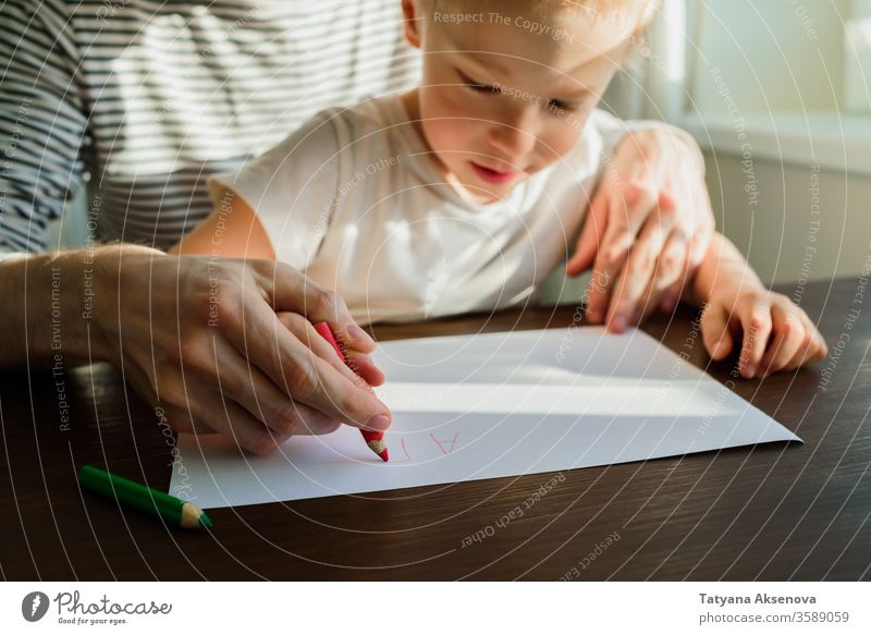 Father teaching child to write or draw education home Homeschooling father writing learning kid homework teacher people sitting parent family pencil childhood
