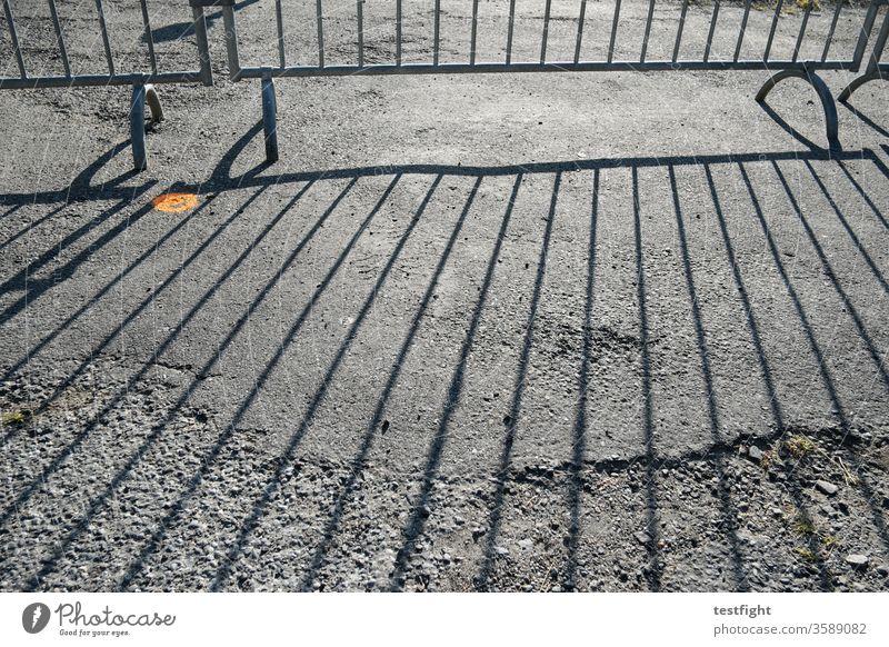 crowd barriers cordon Grating Fence mobile Divide Shadow shadow cast Sunlight Ground Tar Asphalt dilapidated Back-light