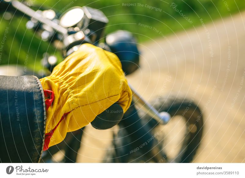 Biker's hand with gloves grabbing the handlebar yellow detail motorcycle vintage biker motorbike man custom retro rider vehicle transport young adult one people