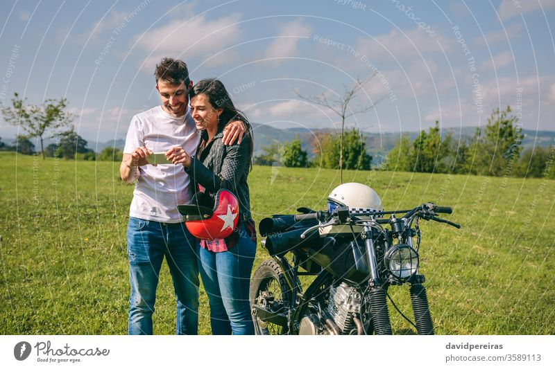 Couple looking mobile with a motorcycle happy couple smartphone picture video trip man smiling cell phone embracing motorcycle helmet custom attractive built