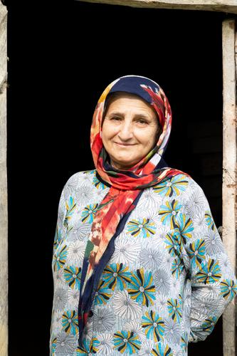 Portrait of a Muslim woman in traditional cloth in front of wooden door frame taleshi local rural countryside travel elderly indoor building lifestyle people