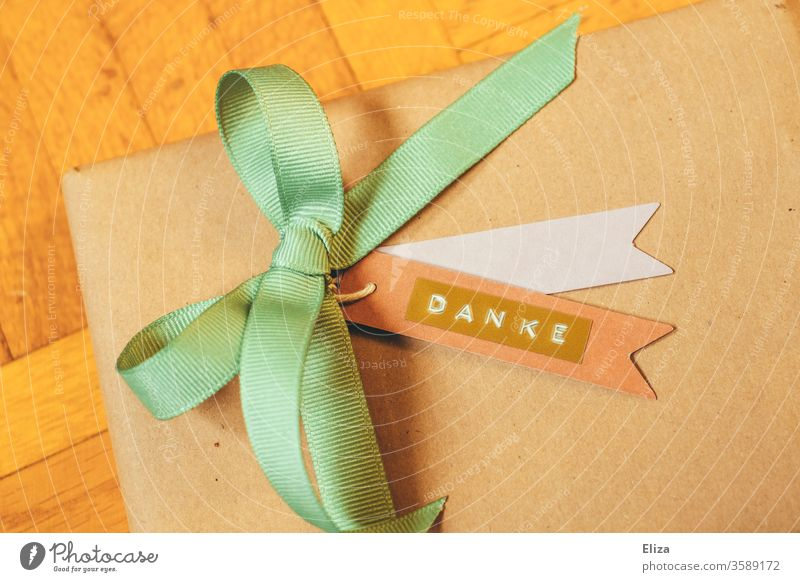 A gift with a ribbon and a pendant with the word thank you written on it. Gratitude. Thank you. I'll take care of it. Gift Packaged Bow wrapped Trailer authored