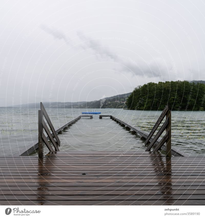 Wet wooden boards of a bathing jetty, a wooden railing into the lake, a barrier in the lake, a blue bathing island, all in rainy grey weather
