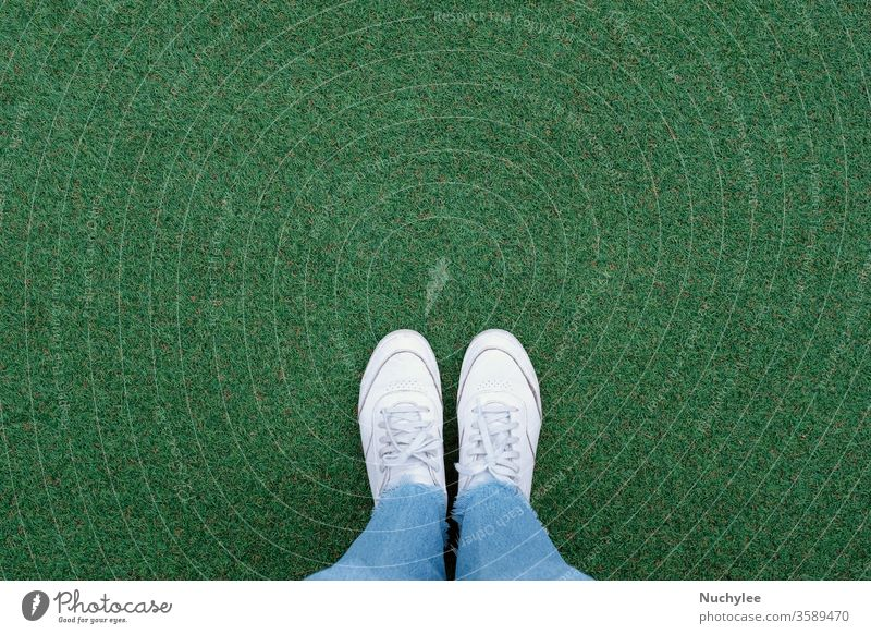 Selfie of feet in white sneakers shoes on green grass background with copy space, spring and summer with fashion lifestyle concept outdoor adventure photo pair