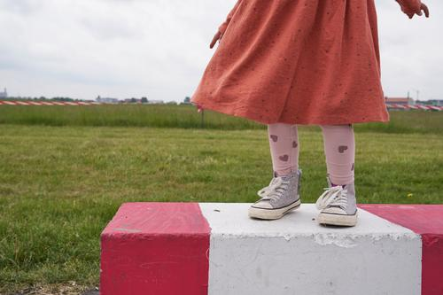 Girl with dress and sneakers stands on a red and white striped concrete barrier on the Tempelhofer Feld, in the background a meadow and red and white barrier tape