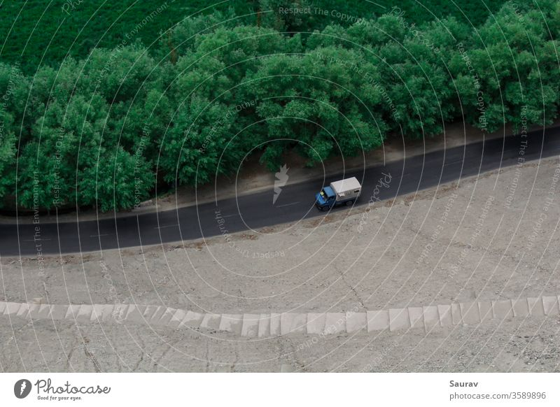 An aerial view of a moving truck on an empty road separated by green trees and the barrens. transportation car truck transportation travel landscape aerial shot