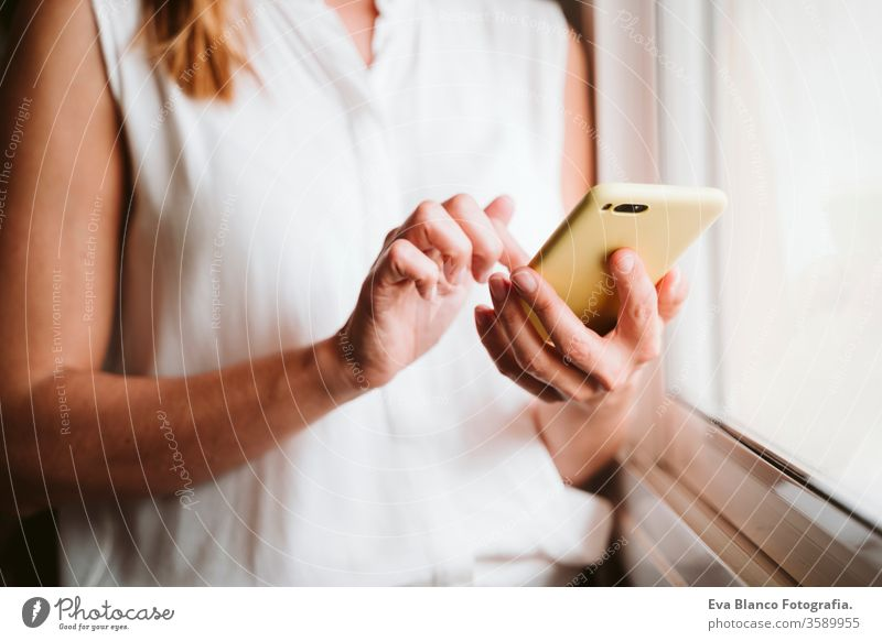 unrecognizable young woman at home using mobile phone by the window technology daytime office work home business stay home stay safe lifestyle working internet