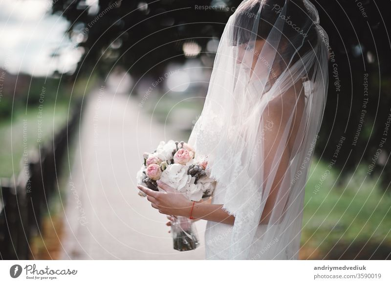 Beautiful young bride in a white luxury dress and in a bridal veil with a bouquet of flowers posing outdoor. wedding portrait. copy space beauty beautiful