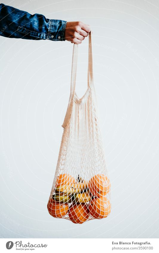 woman han holds a modern shopping bag made of white textile with orange. front view, white background. zero waste concept Orange cotton bag no waste fruits
