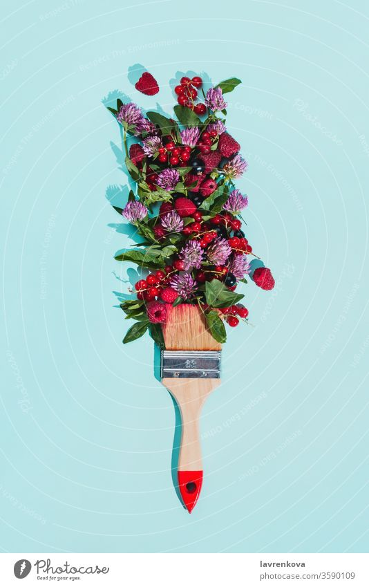 Bristle painting brush with various berries, flowers and leaves on pastel blue background diet harvest berry fresh blossom bouquet bristle bunch clover concept