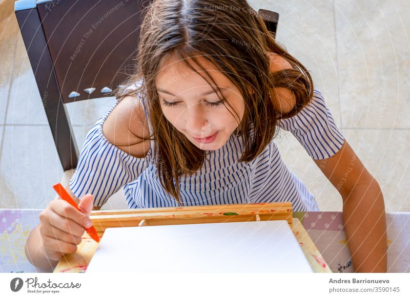 Pretty little girl dressed in a white and blue striped dress drawing on an easel to paint fun happiness education happy vibrant study playful joyful creative