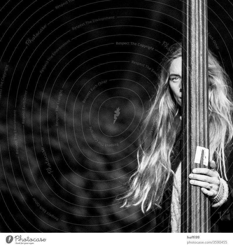 the young woman, half hidden behind the lamppost, looks into the camera Young woman Face of a woman blurred background 18 - 30 years Adults Strand of hair